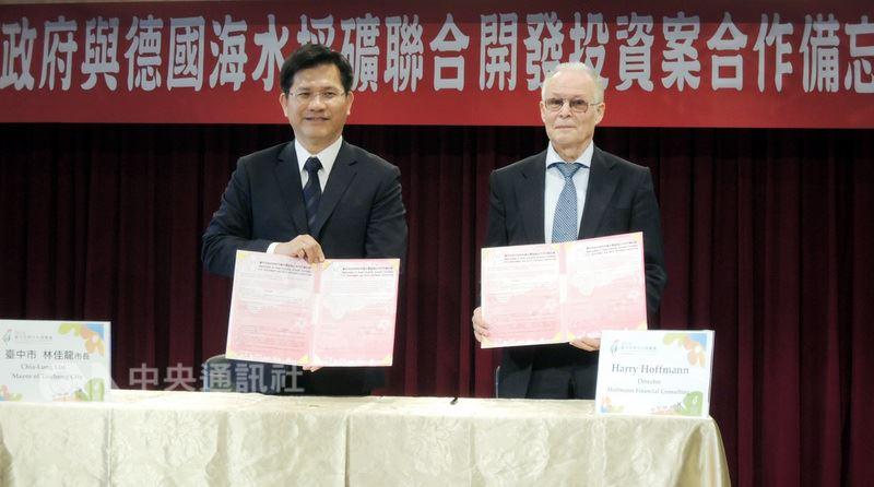 台中市長林佳龍(左)6日在台中市政府與霍夫曼諮詢公司總裁哈利.霍夫曼(右)簽訂「海水採礦聯合開發投資案」合作備忘錄,事後卻爆出一人公司爭議。(中央社檔案照片)
