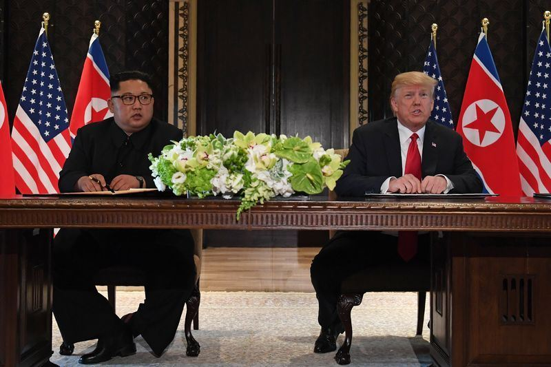 美國總統川普(右)與北韓領導人金正恩(左)12日完成歷史性峰會。(檔案照片/法新社提供)