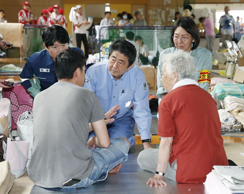 日本因破紀錄暴雨而遭遇30多年來最嚴重水患,首相安倍晉三(中)11日前往其中一個受災最嚴重地區視察。(共同社提供)