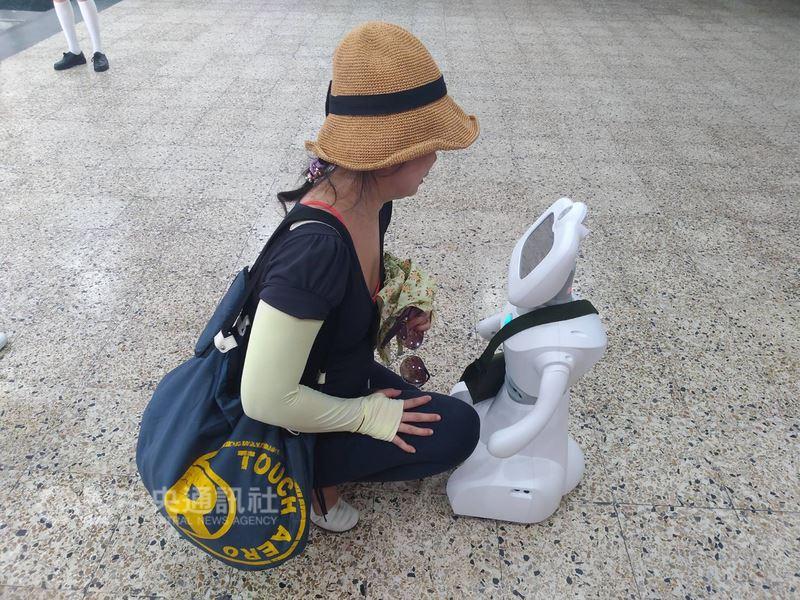 台北市私立開南商工13日特別安排照顧服務科的家用機器人「開寶」背起小書包,協助引導高中職免試入學新生報到,也與一同前來的家長們互動。(開南商工提供)中央社記者梁珮綺傳真 107年7月13日