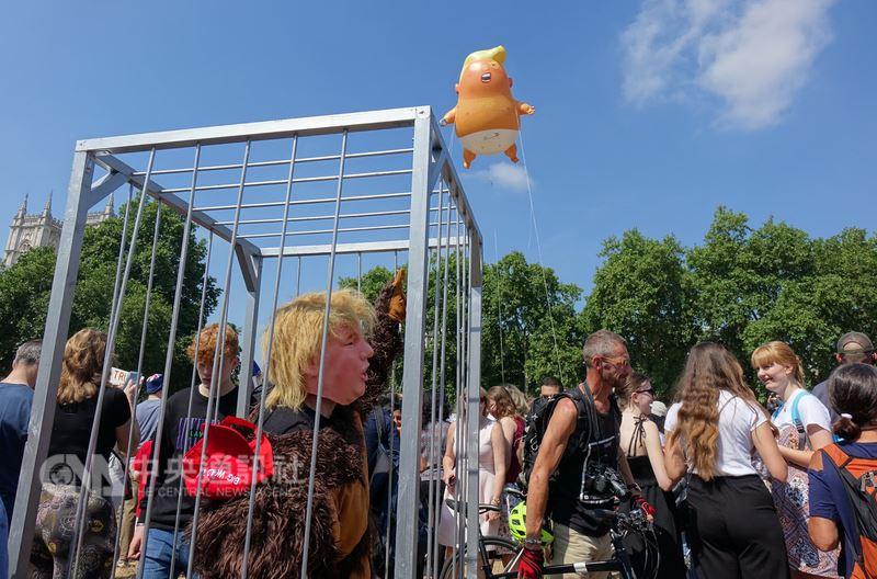抗議美國總統川普訪英,「川普嬰兒」氣球13日在國會前廣場施放,還有人打扮成川普猩猩,自囚牢中。中央社記者戴雅真倫敦攝 107年7月13日