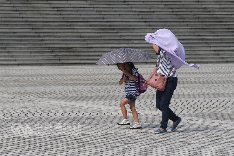 全台各地30日高溫炎熱,民眾午後在缺乏遮蔽物的台北中正紀念堂廣場行走,也撐起傘、拿出衣物以遮蔽豔陽。中央社記者徐肇昌攝 107年7月30日