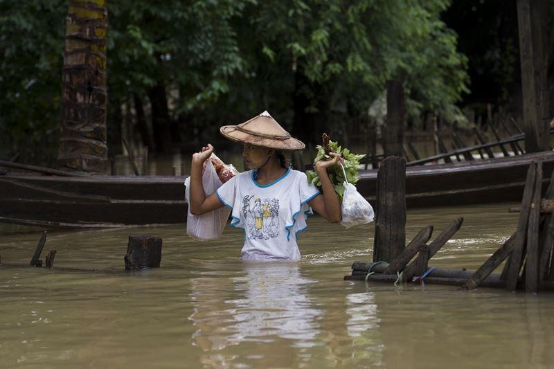 熱帶季風雨導致中南半島國家遭受洪患,緬甸有近15萬人流離失所。圖為民眾在緬甸勃固省被水淹沒的街道上行走。(法新社提供)