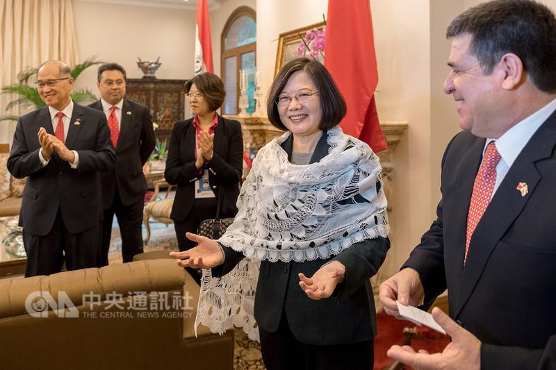 將卸任的巴拉圭總統卡提斯(右)在巴拉圭時間14日送給總統蔡英文(右2)巴拉圭特色織法「蜘蛛繡」披肩,蔡總統披上披肩後,直說很漂亮,還主動要求拍照。(總統府提供)中央社記者葉素萍傳真 107年8月15日