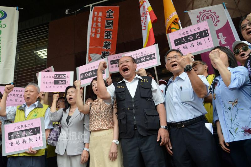 第33次基本工資審議會議16日在勞動部舉行,勞方各工會委員與代表在進入會場前以口號及標語表達勞方調漲基本月薪與時薪的訴求。中央社記者孫仲達攝  107年8月16日
