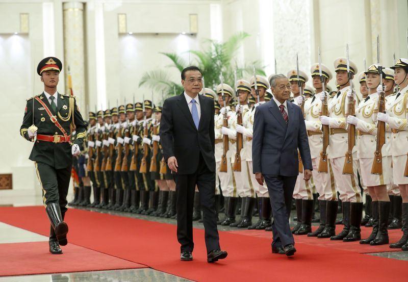 中國國務院總理李克強(中)20日與馬來西亞總理馬哈地(右)舉行會談。(檔案照片/中新社提供)