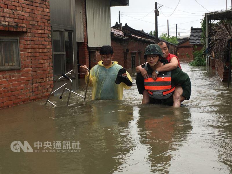 因熱帶低壓帶來的豪雨襲擊南台灣。圖為陸軍南區聯合測考中心官兵協助嘉義布袋、東石及新港地區執行民眾撤離。(國防部提供)中央社記者劉麗榮傳真 107年8月24日