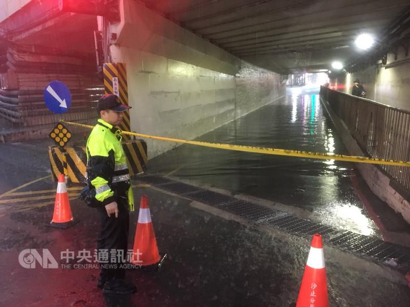 新北市8日午後強降雨造成汐止部分地區積水,中興路上的涵洞積水嚴重,警方派員到場拉起封鎖線並在旁警戒,以防車輛誤入。(民眾提供)中央社記者王朝鈺傳真 107年9月8日