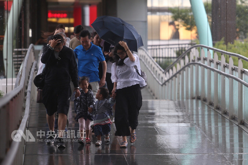 受鋒面和對流旺盛影響,中央氣象局9日對北北基發布超大豪雨特報,陽明山24小時累積雨量已經超過500毫米,預計10日雨勢才會趨緩。風雨大,在信義商圈天橋上行走的民眾都受到雨勢波及。中央社記者吳家昇攝 107年9月9日