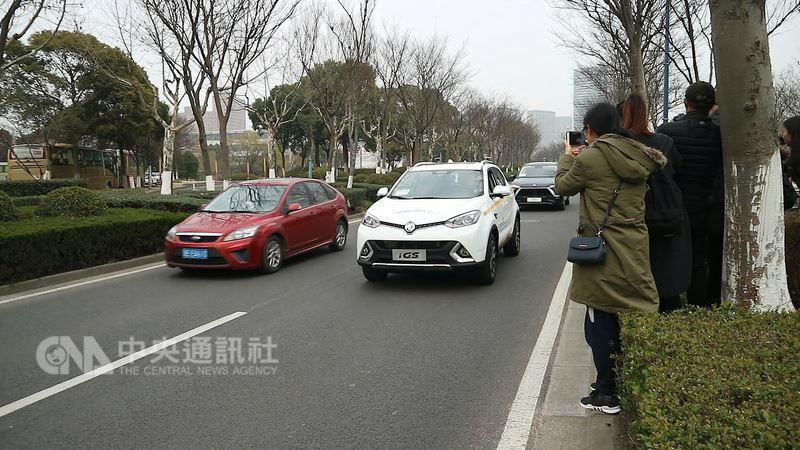 無人駕駛車輛(白色)上路後,時速均控制在40公里至60公里間,且一路閃黃燈,提醒用路人注意,卻有部分駕駛誤以為車輛故障,有些選擇保持安全距離,更多人則是踩油門超車。中央社記者陳家倫上海攝  107年3月1日