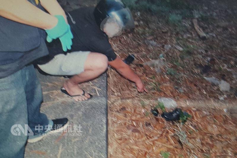 台南市一名余姓男子18日疑因向房客陳姓男子(蹲者)催繳房租,遭對方騙到山區殺害。警方19日帶陳男到案發現場,找到凶器等證物。(翻攝畫面)中央社記者楊思瑞台南傳真 107年3月19日