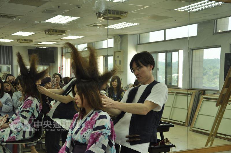曾為日本知名歌手安室奈美惠做頭髮造型的造型師山中康裕(右),受邀到彰化私立建國科技大學美容系進行示範教學,向美容系師生介紹日本當下流行的髮妝造型並交流心得。(建國科大提供)中央社記者吳哲豪傳真 107年3月23日