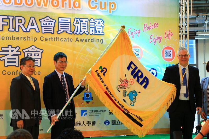 科技部爭取到世界盃智慧機器人足球賽主辦權,8月在台中登場,13日由大會主席包傑奇(Jacky Baltes)(右)授旗給科技部長陳良基(左2),象徵賽事啟動。中央社記者蘇木春攝 107年4月13日