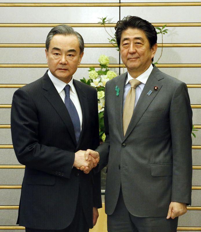 日本首相安倍晉三(右)16日在東京會見中國國務委員兼外交部長王毅(左),除交換朝鮮半島意見外,均表示願兩國關係全面改善並重回正軌。(共同社提供)
