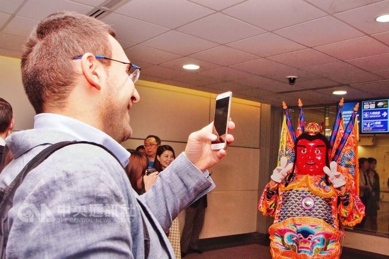 法國航空公司由巴黎飛往台北的首航航班,17日上午抵達桃園國際機場,電音三太子現身接機,讓許多法國旅客拿出手機合照留影。中央社記者吳睿騏桃園機場攝 107年4月17日