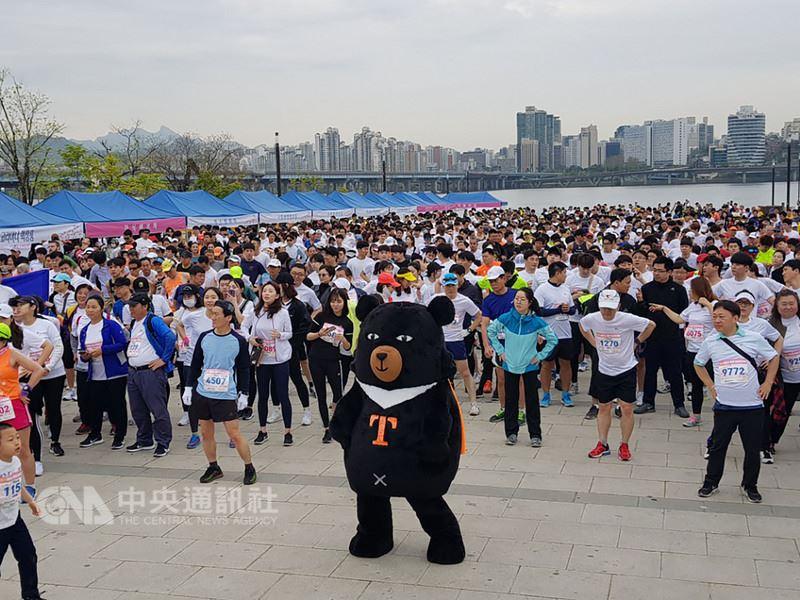 台灣觀光代言人喔熊22日早上與參加漢江汝矣島櫻花馬拉松,與選手們一起暖身,現場熱鬧非凡。(觀光局提供)中央社記者姜遠珍首爾傳真  107年4月22日