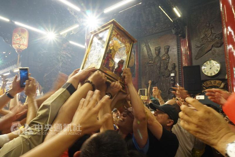 大甲鎮瀾宮媽祖回鑾安座,信徒們伸長了手,爭相撲向媽祖神龕,希望能夠摸得來年的平安順利。中央社記者趙麗妍攝 107年4月23日