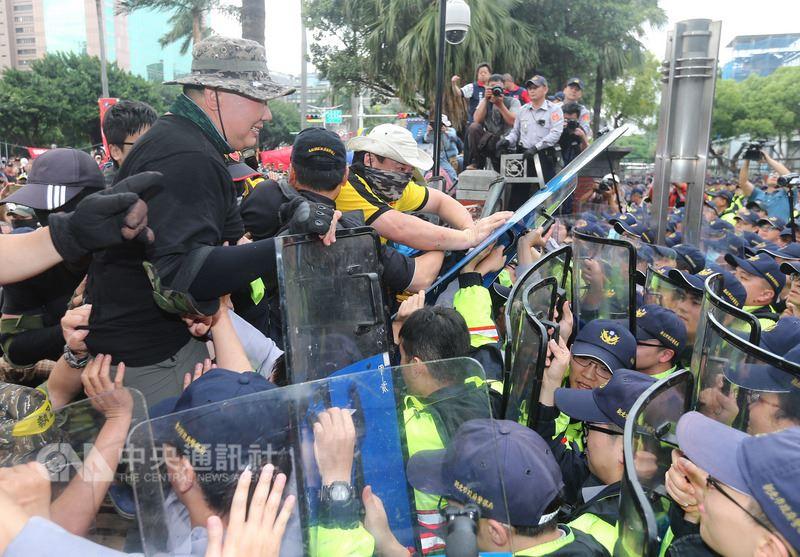 退伍軍人團體八百壯士25日下午在立法院外突然發動攻勢,抗議者拆掉立法院正門部分圍欄,嘗試突破警方防線闖入,警方則以盾牌抵擋。中央社記者徐肇昌攝 107年4月25日