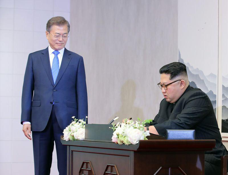 北韓領導人金正恩(右)跨越北緯38度線,成為首位踏上南韓領土的北韓領袖。他呼應南韓「和平,新開始」的宣傳,在貴賓簿寫下「嶄新的歷史從現在開始」。左為南韓總統文在寅。(南北韓峰會共同採訪團提供)