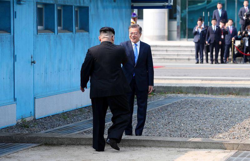 兩韓峰會27日登場,北韓領導人金正恩(左)於台北時間8時30分跨越北緯38度的軍事分界線,南韓總統文在寅(右)親自迎接。(韓聯社提供)