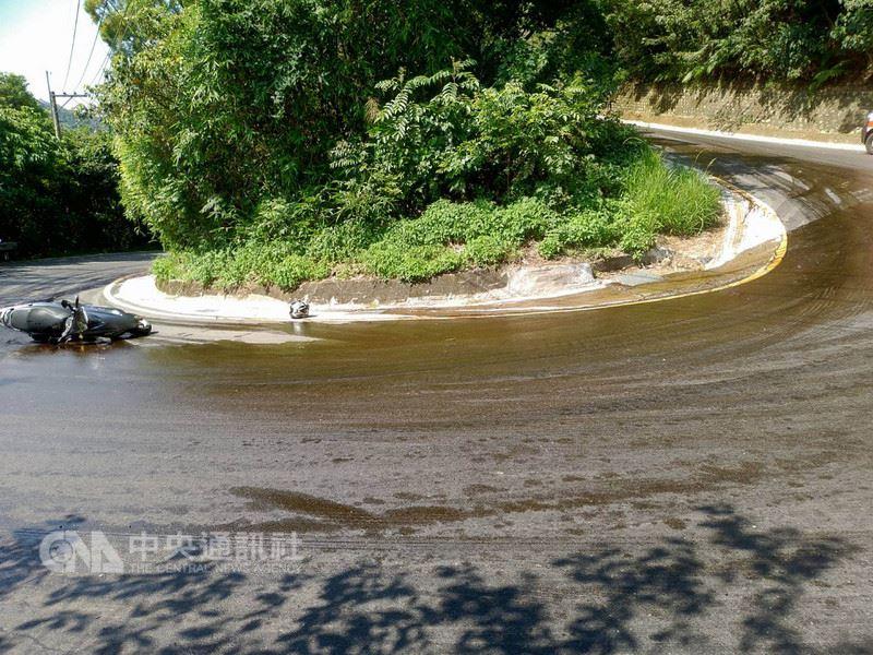 一家環保公司人員18日在林口區山路上打翻廢棄食用油,造成路面濕滑,3名機車騎士及1名女警騎車經過時滑倒,所幸均為輕傷。消防人員到場後將4人送醫治療。(翻攝照片)中央社記者林長順傳真  107年5月18日