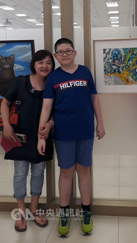 高雄市小港國中學生蘇亦禾(右)罹患「小胖威利症」,他勇敢面對生命挑戰,藉繪畫與游泳闖出一片天,獲選總統教育獎。(高市教育局提供)中央社記者程啟峰高雄傳真 107年5月18日