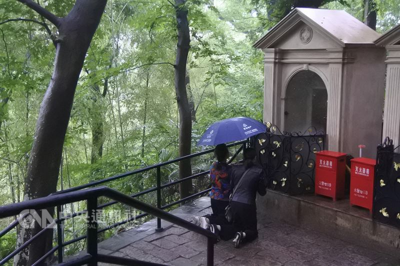 5月是天主教的聖母月,許多信徒到上海佘山天主教堂朝聖。圖為兩名女子19日在朝聖途中,向其中一幅耶穌受難的「苦路圖」禱告、讀經。(資料照片)中央社記者張淑伶上海攝  107年5月20日
