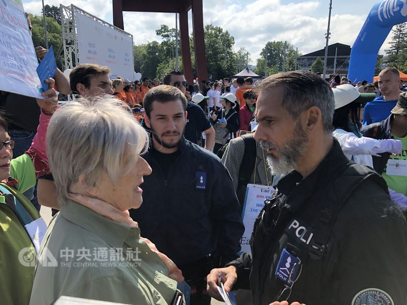 世界衛生組織20日舉辦健走活動,台灣宣達團手持Taiwan標語遭警方阻止,並盤問協助報名的關懷地球基金會副總裁傅莉(左)。 中央社記者戴雅真日內瓦攝 107年5月20日