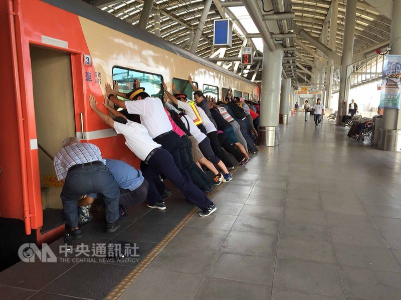 台鐵屏東站27日上午有一名婦人強行推折疊門要上車,由於火車在緩慢行駛中,婦人滑落卡在月台與火車間空隙,列車緊急停駛,台鐵工作人員與月台上其他旅客合力推車廂救人。(台鐵提供)中央社記者汪淑芬傳真 107年5月27日
