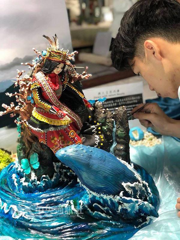 明道中學餐飲管理科學生王奕鈞,日前參加「新加坡國際美食競賽」,拿下翻糖組銀牌。他將作品命名為「與大自然共舞」,以台灣在地素材作為設計靈感,創作出一個與大海、鯨魚、台灣原生蝴蝶共舞的「原住民公主」,連部落公主的眼睫毛都是一根一根植上去的,工法相當精細。(明道中學提供)中央社記者蘇木春傳真 107年5月27日