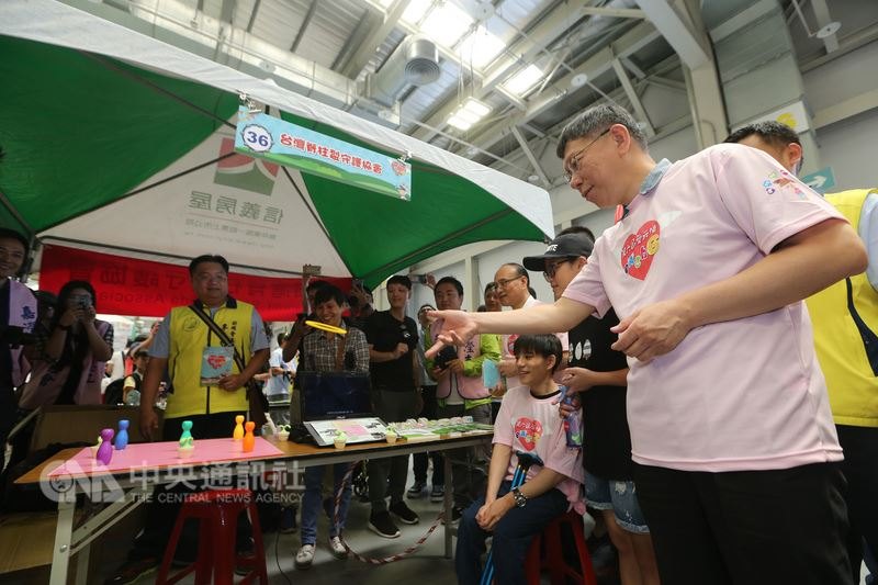 台北市長柯文哲(右)27日在花博爭艷館出席第6屆愛天使園遊會,在參觀攤位時下場玩遊戲。中央社記者吳家昇攝 107年5月27日
