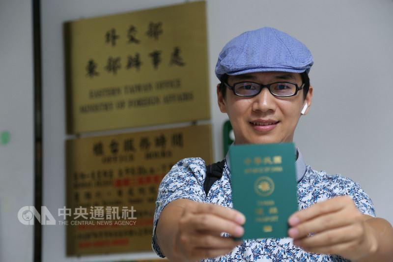 中國公民記者周曙光依親移居台灣取得身分證後,8日拿到中華民國護照,他開心地說,以後到許多國家都免簽證,比起中國護照好用太多了。中央社記者李先鳳攝 107年6月8日