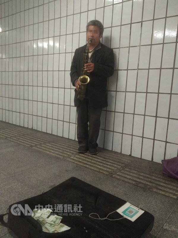 行動支付暢行中國,圖為一名在北京某處地下道的行乞者,旁邊放著二維碼牌接受捐款。中央社記者周慧盈北京攝 107年6月9日