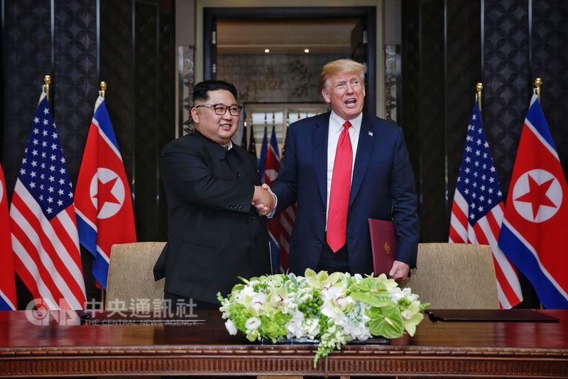 美國總統川普(右)12日與北韓領袖金正恩(左)在新加坡舉行歷史性峰會,兩人共同在媒體面前簽署文件後握手致意。(新加坡通訊及新聞部提供)中央社記者裴禛新加坡傳真 107年6月12日