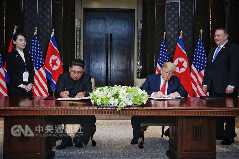 美國總統川普(右2)12日與北韓領袖金正恩(左2)在新加坡舉行峰會,結束工作午宴後,兩人共同在媒體面前簽署文件。(新加坡通訊及新聞部提供)中央社記者裴禛新加坡傳真 107年6月12日