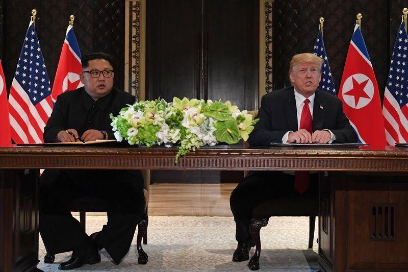 美國總統川普12日與北韓領袖金正恩舉行歷史性峰會,兩人共同在媒體面前簽署文件。(法新社提供)