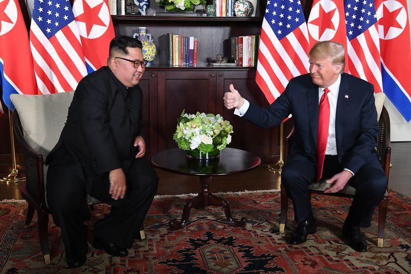 美國總統川普(右)與北韓領導人金正恩(左)12日在新加坡順利舉行歷史性高峰會,獲國際肯定。(法新社提供)