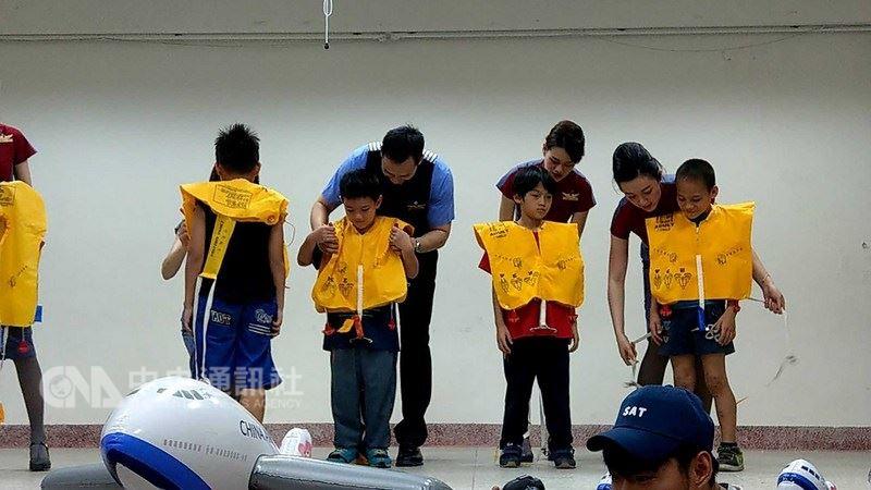 中華航空公司「愛心趴趴走團隊」一行約40人,14日來到空服員羅祖兒的母校花蓮縣秀林國小,學童手持自製護照與機票,模擬體驗登機出國流程,學習登機禮儀、機上安全,並認識澳洲等國家特色。中央社記者李先鳳攝 107年6月14日