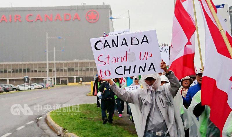 加拿大台僑在加航蒙特婁總部前,高舉「加拿大勇敢對抗中國」標語,示威抗議,表達反對加航屈服中國、更改台灣名稱的強烈不滿。(加拿大台僑葉國基提供)中央社記者胡玉立多倫多傳真  107年6月15日