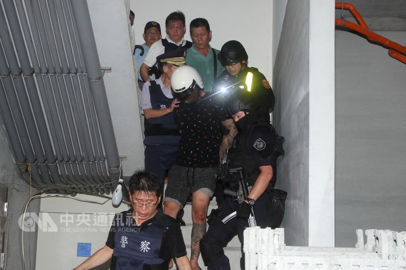台南市17日清晨發生通緝犯拒捕並奪走警槍逃逸事件,嫌疑人楊姓男子(前中)下午在一處建築工地落網。 中央社記者楊思瑞攝 107年6月17日