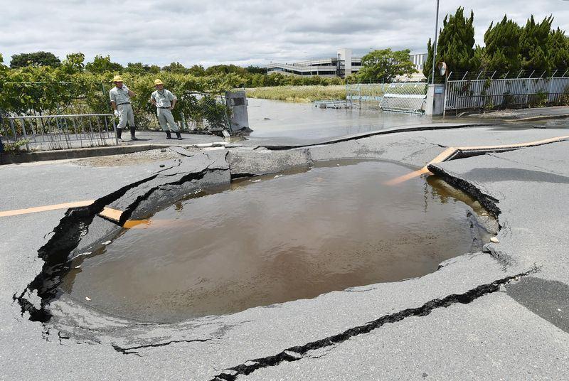 大阪北部18日上午7時發生規模6.1強震,導致一處水管破裂,道路塌陷。(共同社提供)
