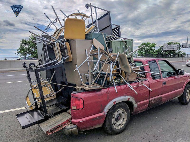 麻州州警20日在臉書專頁發表3張照片,照片中一輛紅色小貨車車斗堆滿了課桌椅、置物櫃及貨架,造型宛如刺蝟。(圖取自麻州州警臉書facebook.com/MassStatePolice)