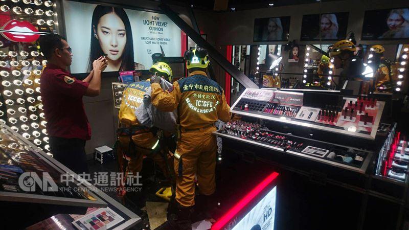 台中市北區一家百貨公司25日晚間發生一名男子墜樓,卡在一樓化妝品區天花板的意外,消防局獲報趕到現場,將男子送醫急救。(翻攝畫面)中央社記者蘇木春傳真 107年6月25日