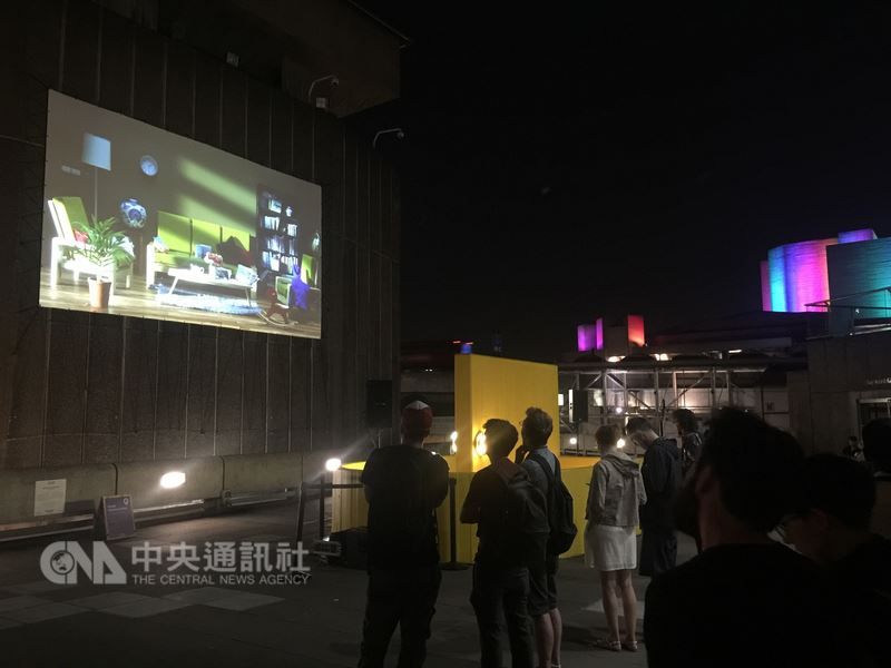 台灣藝術家袁廣鳴的錄像作品「棲居如詩」7日晚間在南岸藝術中心外牆徹夜巨型投影,溫馨的居家客廳突然瞬間爆炸摧毀,震撼力十足,讓觀眾驚呼連連。(駐英文化處提供)中央社記者戴雅真倫敦傳真 107年7月8日