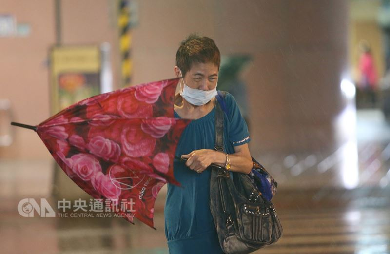 颱風瑪莉亞10日來襲,台北市區下午開始陸續有間歇雨勢,晚間風雨增強,且不時有強陣風,街頭撐傘民眾被瞬間強風吹歪了傘。中央社記者鄭傑文攝 107年7月10日