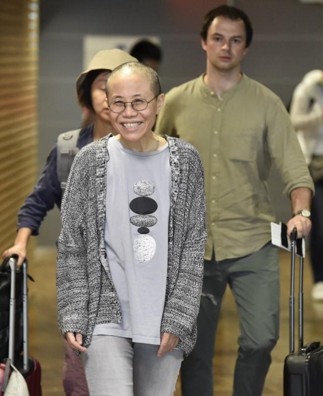 中國諾貝爾和平獎得主劉曉波遺孀劉霞(前)遭軟禁8年後,10日重獲自由,將在德國展開新生活。圖為劉霞抵達芬蘭赫爾辛基機場轉機時露出笑容。(路透社提供)