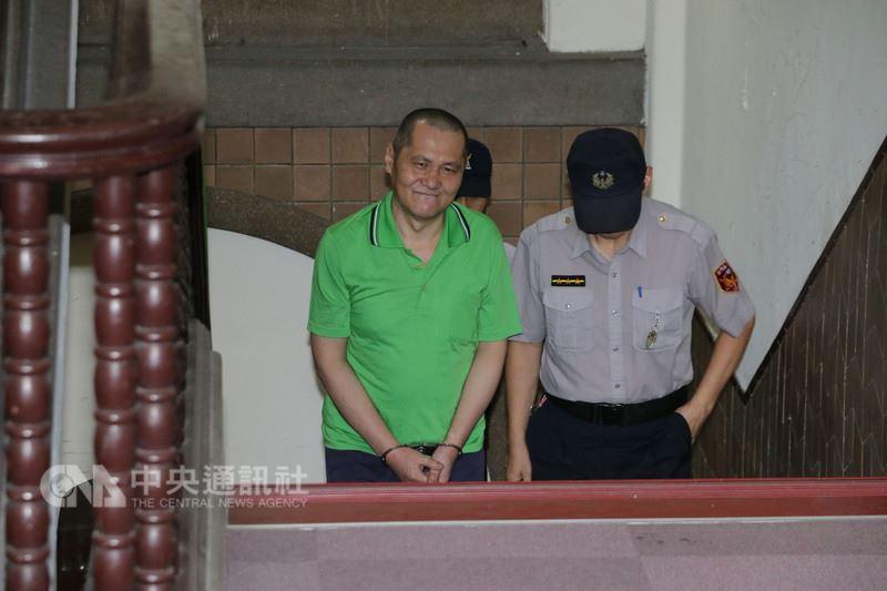 男子翁仁賢(前左)除夕縱火燒死父母親友,造成6死4傷,二審遭判死刑。案經最高法院發回,高院更一審12日開庭,遭羈押的翁仁賢被法警提解出庭時露出微笑。中央社記者蕭博文攝  107年7月12日