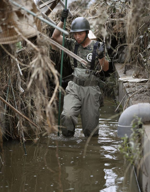在豪雨風災後,日本搜救人員12日持續搜索數十名仍下落不明的民眾。(共同社提供)