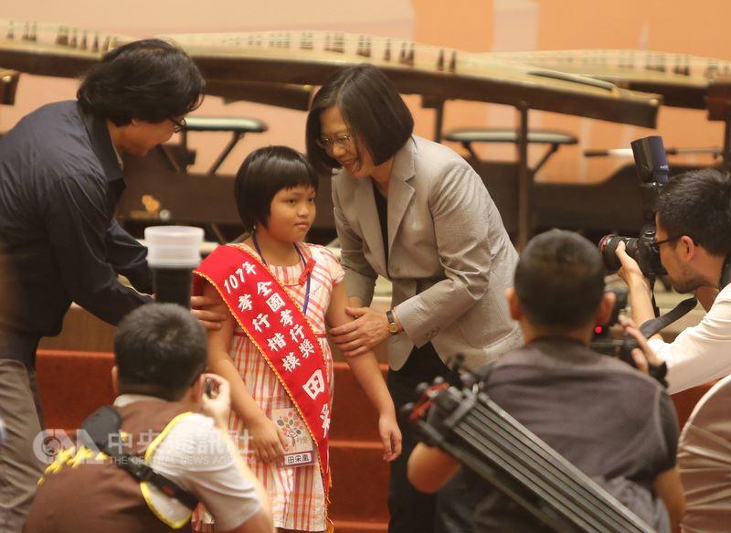 南投8歲女童田采凰(後左2),平日和哥哥照顧中風的父親,13日獲頒107年全國孝行獎,總統蔡英文(後左3)還請在場所有人掌聲鼓勵。中央社記者張榮祥台南攝  107年7月13日