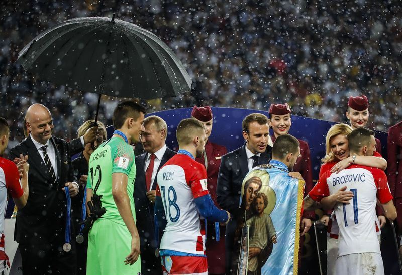 克羅埃西亞總統季塔洛維奇(右2)15日出席世界盃足球賽閉幕典禮,一一擁抱決賽兩支球隊的每一位球員。(安納杜魯新聞社提供)